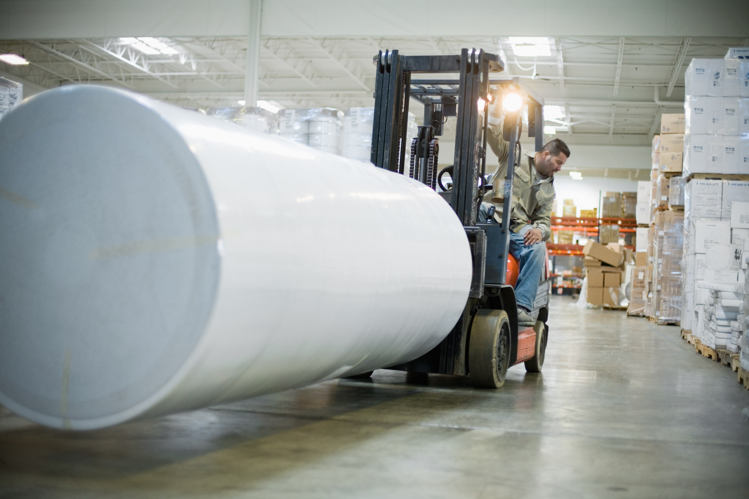 Warehouse Worker Driving Forklift with Roll of Paper